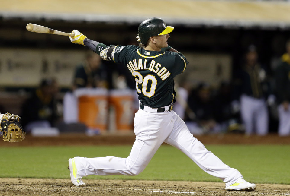 Photo - Oakland Athletics' Josh Donaldson swings for an RBI single off Washington Nationals' Rafael Soriano in the ninth inning of a baseball game Saturday, May 10, 2014, in Oakland, Calif. (AP Photo/Ben Margot)