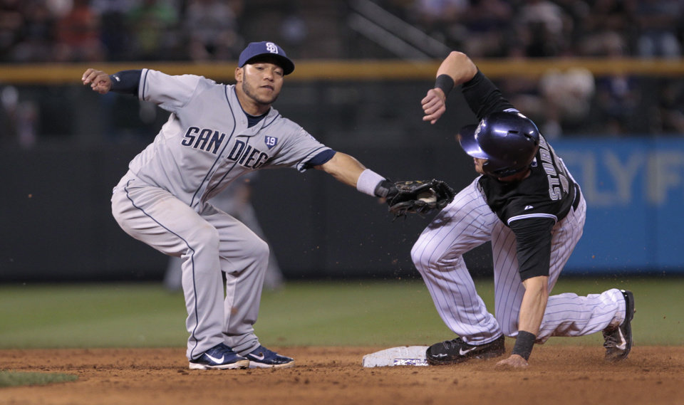 Photo - Colorado Rockies' Drew Stubbs (13) avoids the tag of San Diego Padres shortstop Alexi Amarista (5) as Stubbs steals second base in the eighth inning of a baseball game in Denver on Tuesday, July 8, 2014.(AP Photo/Joe Mahoney)