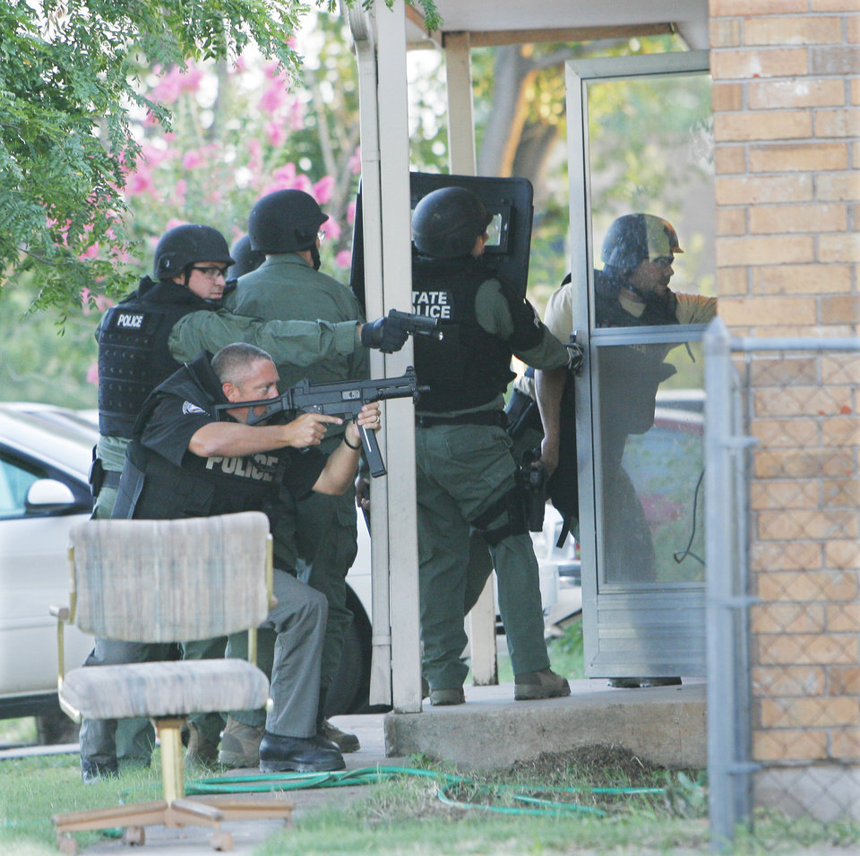 Photo - Oklahoma Bureau of Narcotics agents prepare to enter a home in Anadarko during a meth raid. Oklahoma Bureau of Narcotics executed a large-scale raid Tuesday morning, July 14, 2009, in Caddo County, launching out of Anadarko,   Photo By David McDaniel, The Oklahoman.