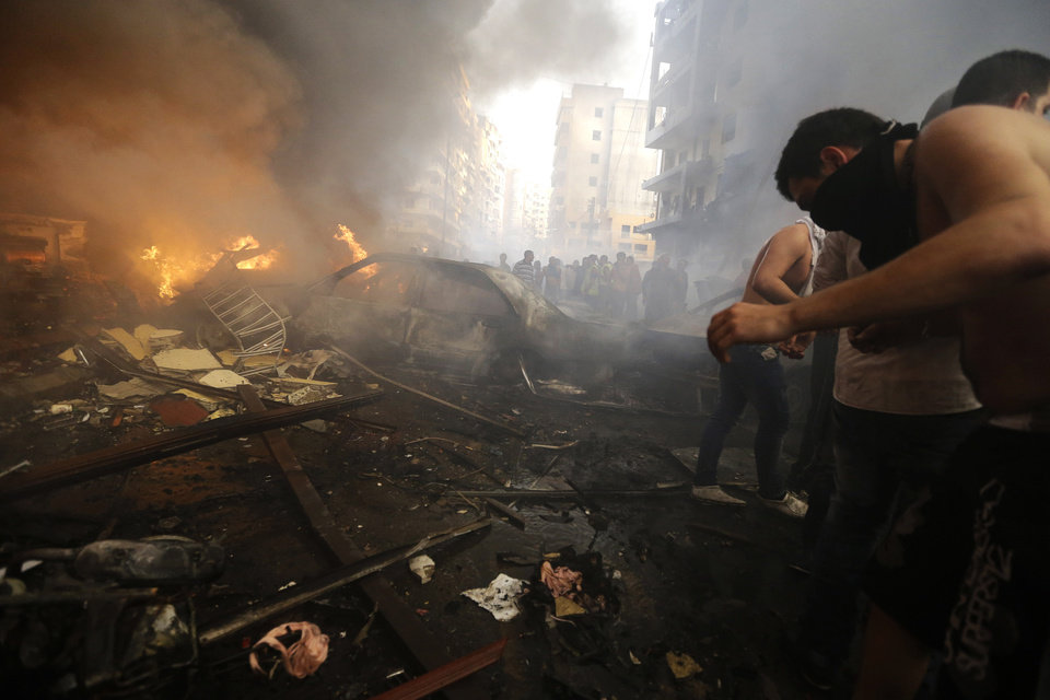 Photo - Lebanese citizens and Hezbollah supporters gather next to burned cars and shops at the site of a car bomb explosion in southern Beirut, Lebanon, Thursday, Aug. 15, 2013. The powerful car bomb ripped through a southern Beirut neighborhood that is a stronghold of the militant group Hezbollah on Thursday, killing people and trapping others in burning buildings, the media said. (AP Photo/Hussein Malla)