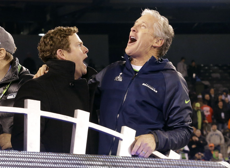 Photo - Seattle Seahawks head coach Pete Carroll, right, celebrates with general manager John Schneider after the NFL Super Bowl XLVIII football game against the Denver Broncos Sunday, Feb. 2, 2014, in East Rutherford, N.J. The Seahawks won 43-8. (AP Photo/Ted S. Warren)
