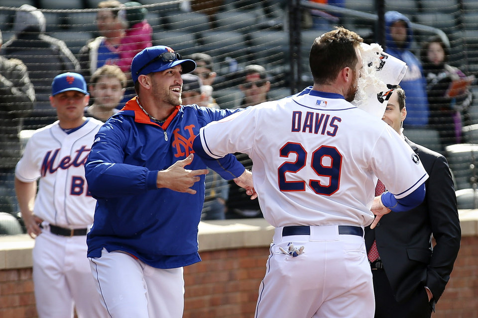 Photo - New York Mets first baseman Ike Davis (29) takes shaving cream to the face by starting pitcher Jonathon Niese after Davis hit a walk-off grand slam in the ninth inning of a baseball game against the Cincinnati Reds at Citi Field, Saturday, April 5, 2014, in New York. The Mets won 6-3. (AP Photo/John Minchillo)
