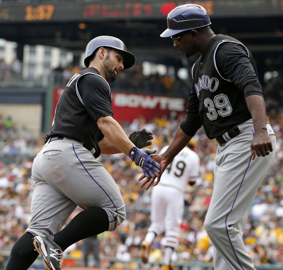 Photo - Colorado Rockies' Michael McKenry, left,  rounds third to greetings from Colorado Rockies third base coach Stu Cole (39) after hitting a solo home run off Pittsburgh Pirates starting pitcher Jeff Locke (49), center rear, during the second inning of a baseball game in Pittsburgh Sunday, July 20, 2014. (AP Photo/Gene J. Puskar)