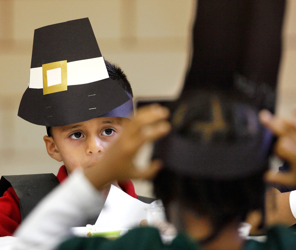 Photo - Angel Rosales watches a classmate adjust his hat while they are seated in the cafeteria for Thanksgiving snacks. Kindergarten students at Rancho Village Elementary School in southwest Oklahoma City dressed as Pilgrims and Indians and feasted on homemade butter they made in their classrooms earlier in the day. They also ate bread, celery and popcorn which the made in the cafeteria  Tuesday afternoon, Nov. 22, 2011.  Photo by Jim Beckel, The Oklahoman