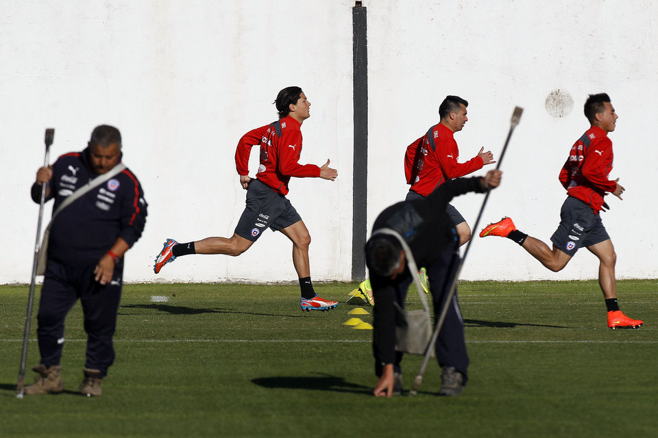 Photo - Chile's players, from left, Miiko Albornoz, Gary Medel and Eduardo Vargas warm-up for a training session in Santiago, Chile, Wednesday, May 28, 2014. Chile will play a friendly match with Egypt in Santiago on Friday prior to competing at the World Cup in Brazil in June. (AP Photo/Luis Hidalgo)
