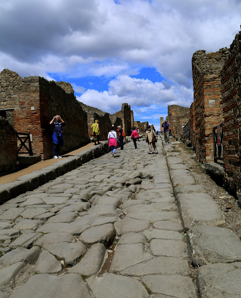 Photo - This May 14, 2014 photo shows a narrow street leading through the ruined town of Pompeii, near modern-day Naples, Italy. Ancient Pompeii was destroyed in A.D. 79 following the eruption of Mount Vesuvius. The marks in the foreground are ruts caused by ancient cartwheels. (AP Photo/Michelle Locke)