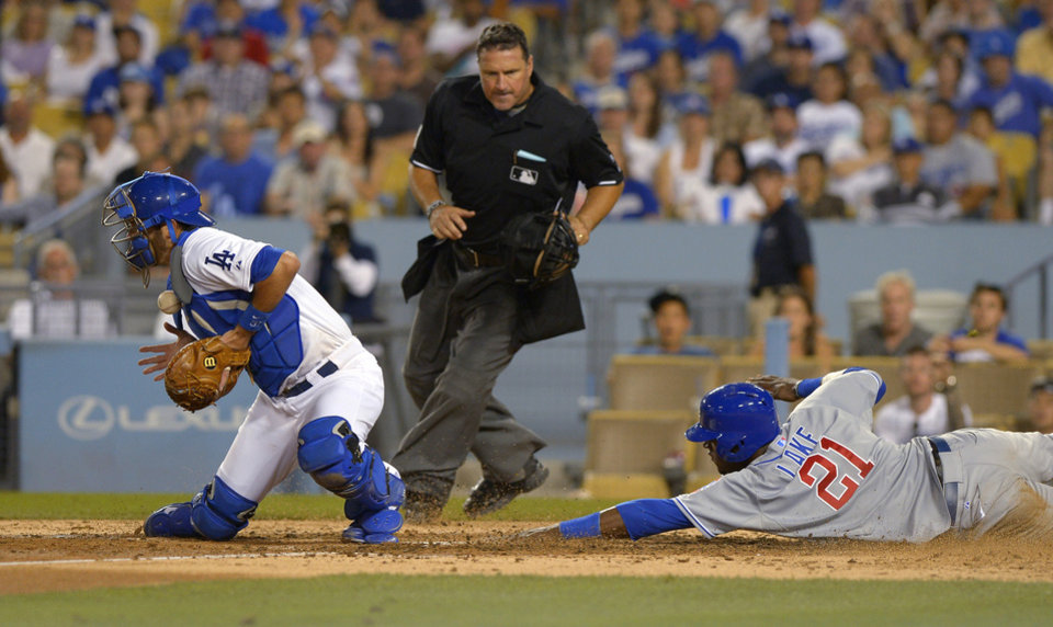 Photo - Chicago Cubs' Junior Lake, right, scores as Los Angeles Dodgers catcher Drew Butera, left, takes a late throw, while home plate umpire Tony Randazzo watches during the seventh inning of a baseball game, Saturday, Aug. 2, 2014, in Los Angeles. (AP Photo/Mark J. Terrill)