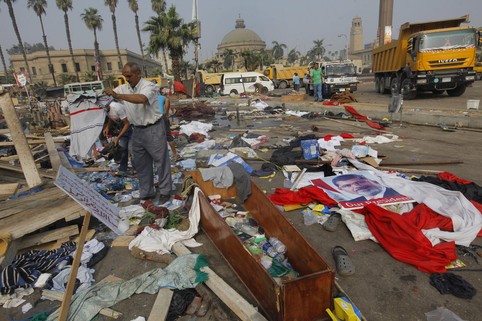 Photo - Egyptians search for valuables among the debris from a protest camp in Nahda Square, Giza, Cairo, Egypt, Thursday, Aug. 15, 2013. Egypt faced a new phase of uncertainty on Thursday after the bloodiest day since its Arab Spring began, with over 300 people reported killed and thousands injured as police smashed two protest camps of supporters of the deposed Islamist president. Wednesday's raids touched off day-long street violence that prompted the military-backed interim leaders to impose a state of emergency and curfew, and drew widespread condemnation from the Muslim world and the West, including the United States. (AP Photo/Amr Nabil)