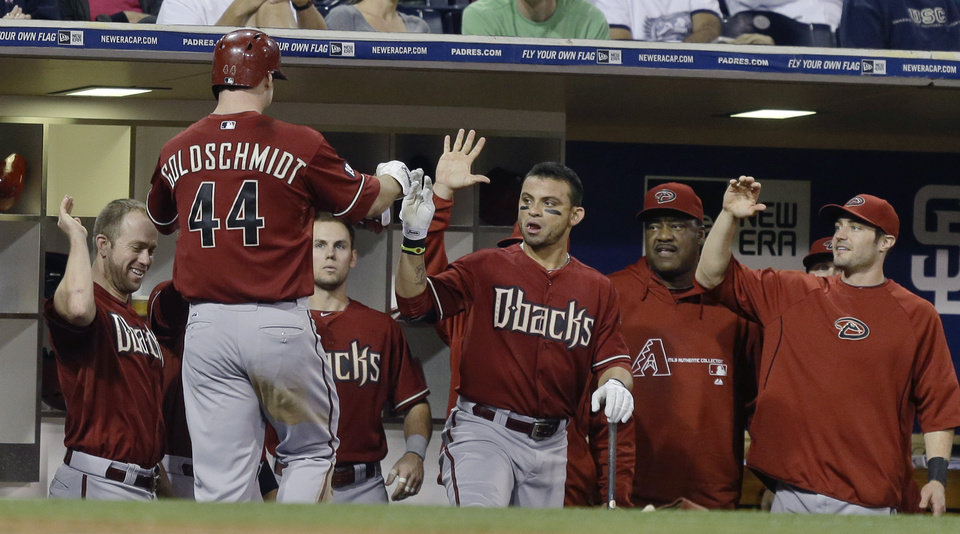 Photo - Arizona Diamondbacks' Paul Goldschmidt is greeted at the dugout after scoring from third on a balk by San Diego Padres starting pitcher Ian Kennedy in the fourth inning of a baseball game Wednesday, Sept. 25, 2013, in San Diego. (AP Photo/Lenny Ignelzi)