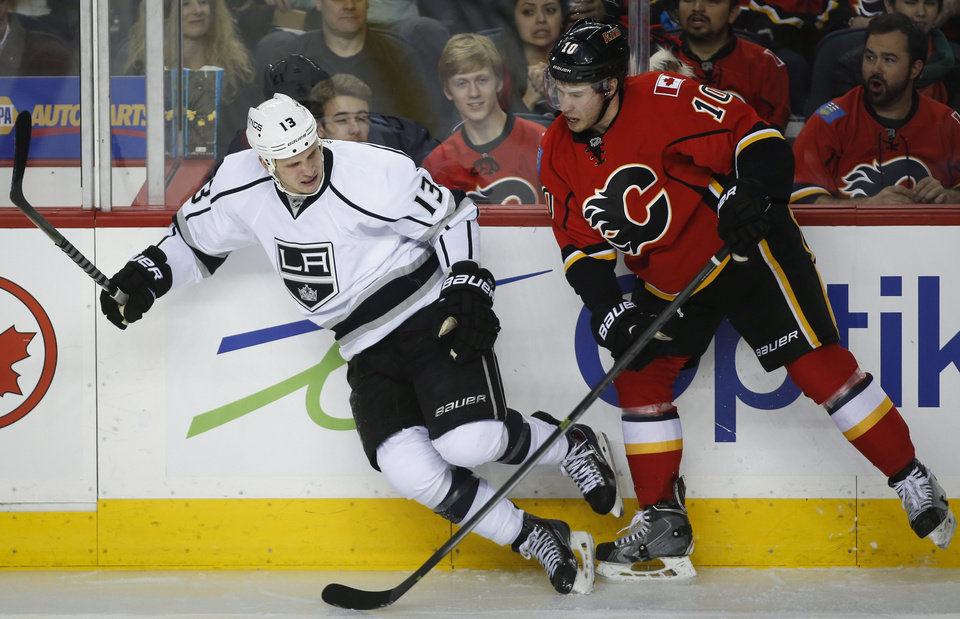 Photo - Los Angeles Kings' Kyle Clifford, left, runs into Calgary Flames' Corban Knight during second period NHL hockey action in Calgary, Alberta, Monday, March 10, 2014. (AP Photo/The Canadian Press, Jeff McIntosh)