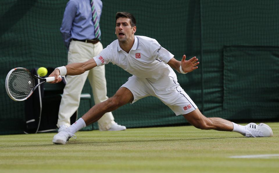 Photo - Novak Djokovic of Serbia plays a return  during the men's singles quarterfinal match against Marin Cilic of Croatia at the All England Lawn Tennis Championships in Wimbledon, London, Wednesday July 2, 2014. (AP Photo/Ben Curtis)