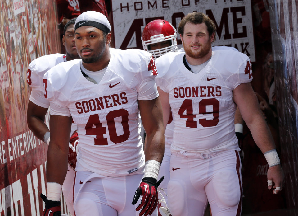 Photo - P. L. Lindley (40) and David Driskill (49) step onto the filed before the annual Spring Football Game at Gaylord Family-Oklahoma Memorial Stadium in Norman, Okla., on Saturday, April 13, 2013. Photo by Steve Sisney, The Oklahoman
