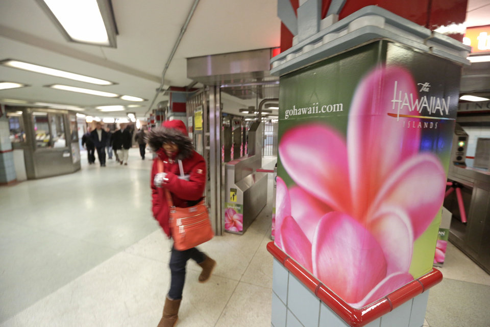 Photo - In this  Wednesday, Feb. 26, 2014 photo, bundled up commuters walk past an advertisement for the Hawaiian Islands near a train stop in Chicago. With yet another polar vortex like storm system bearing down on many parts of the country, suffering Midwesterners dream about being anywhere but home. Florida resorts and other tourist operations have been fueling this with email and other ad campaigns dangling a little sunshine and beach scenes in front of us.  (AP Photo/M. Spencer Green)
