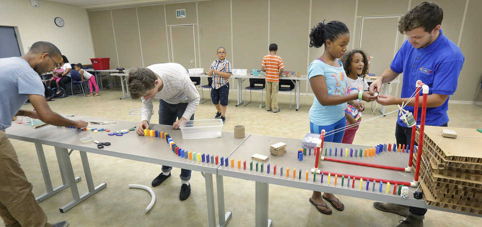 Photo -  Londyn Johnson, 10, and Cora Linden, 9, assist Tyler Troy in setting up a chain reaction experiment. At left, completing another segment of the project, are Felix Linden, who brought his three children to the camp, and Sam Regan. Photo by Jim Beckel, The Oklahoman   Jim Beckel -