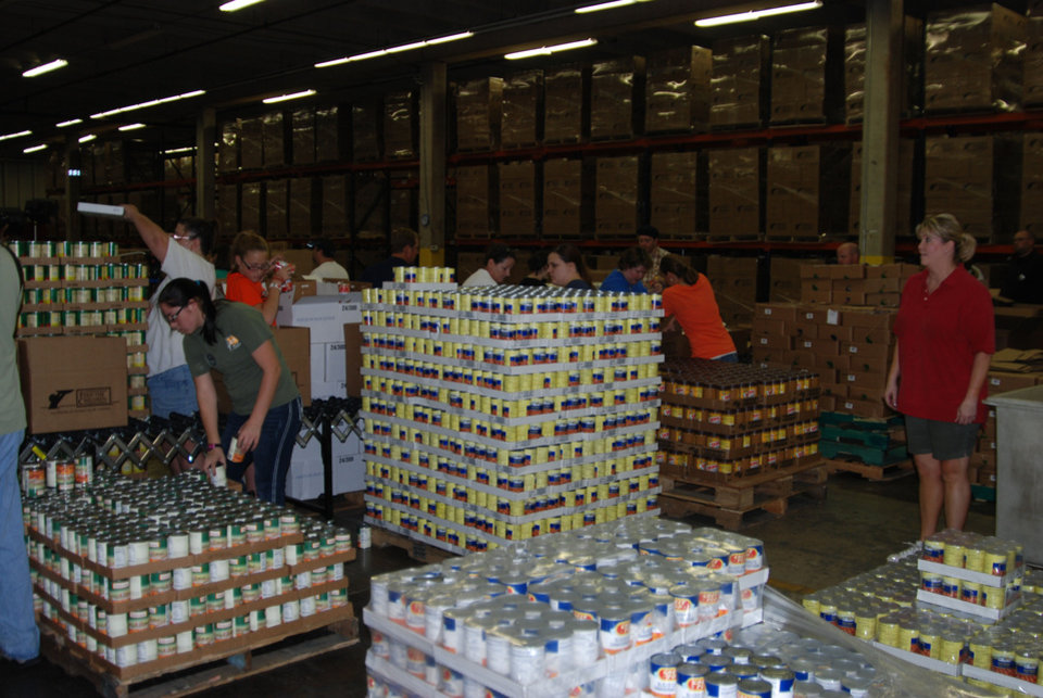 Photo - Volunteers work in a warehouse at Feed the Children headquarters in Oklahoma City. Photo provided.