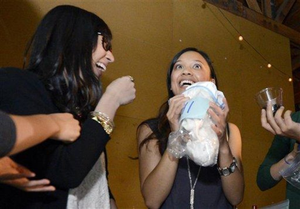 Photo - Jessica Nguyen, right, reacts after smelling a shirt as Angela Abad-Santos looks on during a pheromone party, Friday, June 15, 2012, in Los Angeles. The get-togethers, which have been held in New York and Los Angeles and are planned for other cities, require guests to submit a slept-in T-shirt that will be sniffed by other participants. Then you can pick your partner based on scent. (AP Photo/Mark J. Terrill)