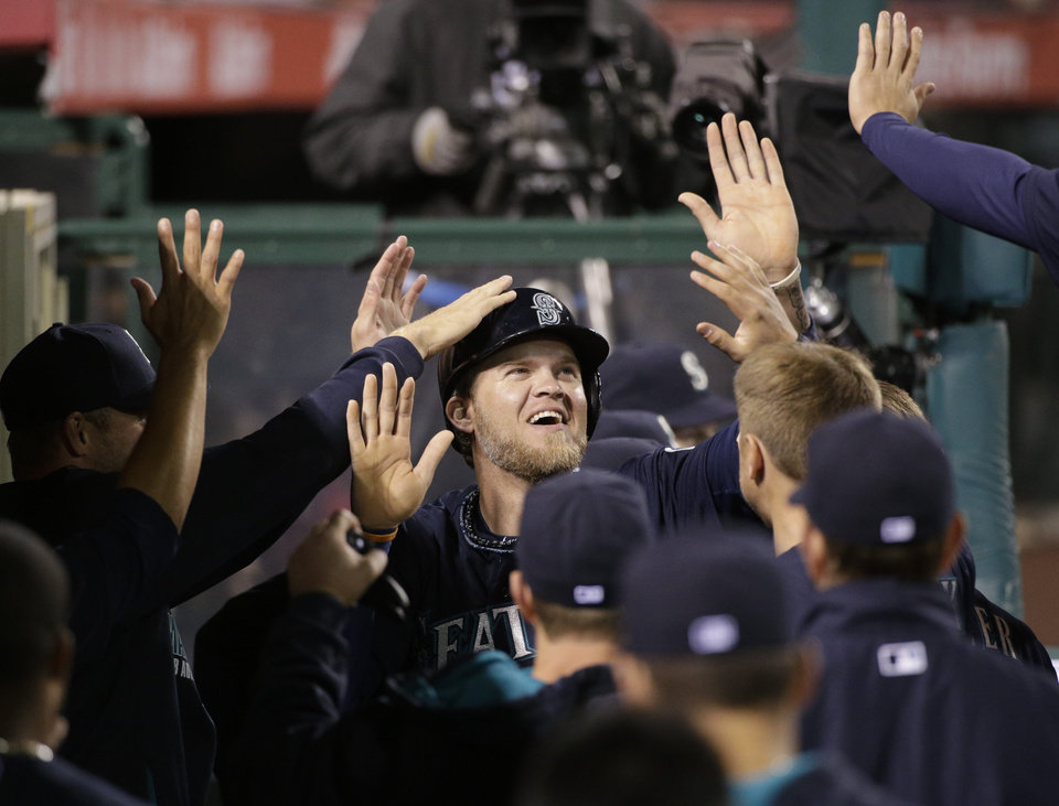 Photo - Seattle Mariners' Corey Hart, center, is greeted by teammates after scoring on a double by Dustin Ackley during the sixth inning of a baseball game against the Los Angeles Angels on Tuesday, April 1, 2014, in Anaheim, Calif. (AP Photo/Jae C. Hong)