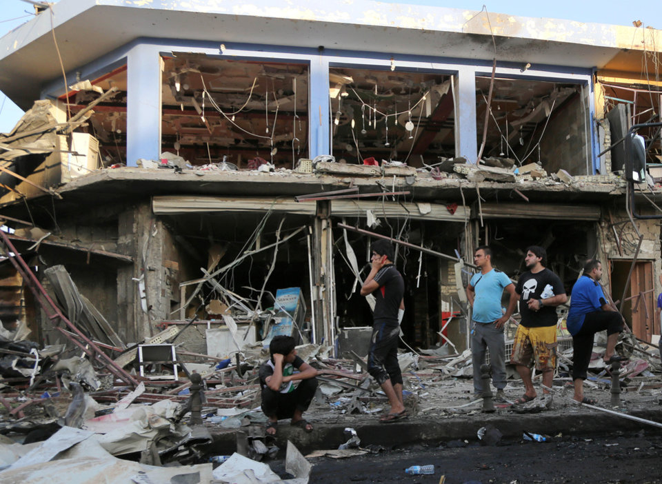 Photo - Civilians inspect the site of a car bomb attack near a restaurant in the southeastern district of New Baghdad, Iraq, Wednesday, Aug. 13, 2014. A string of attacks in and around the capital killed more than a dozen and wounded dozens. (AP Photo/Karim Kadim)
