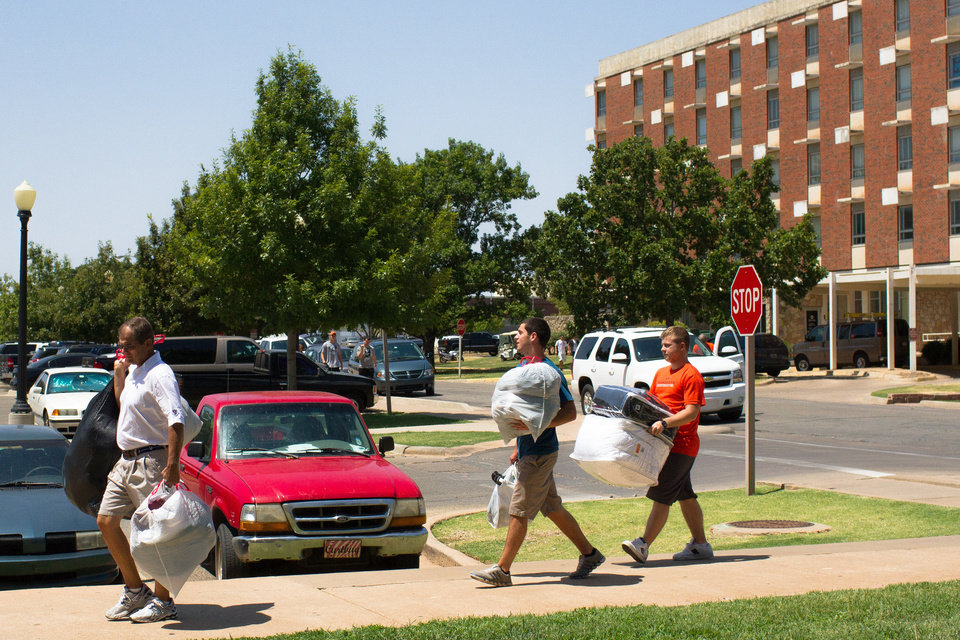 Photo - Larry Maylon, front, helps his son, Michael Maylon, middle, and David Peck move into their residence hall.
