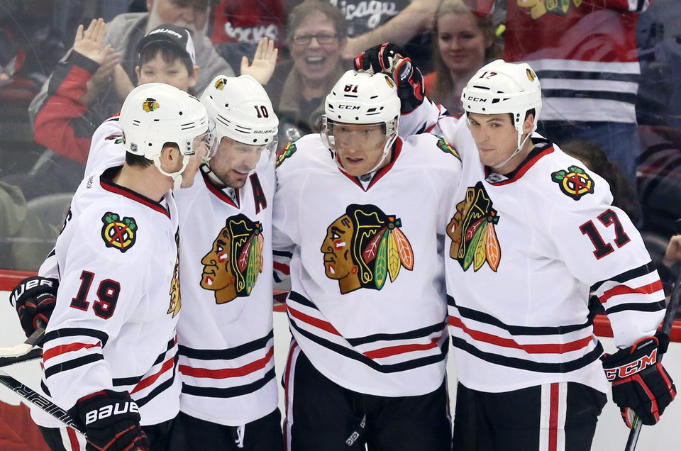 Photo - Chicago Blackhawks' Marian Hossa (81) celebrates his goal with teammates Jonathan Toews (19), Patrick Sharp (10) and Sheldon Brookbank (17) during second-period NHL hockey game action against the Ottawa Senators in Ottawa, Ontario, Friday, March 28, 2014. (AP Photo/The Canadian Press, Fred Chartrand)
