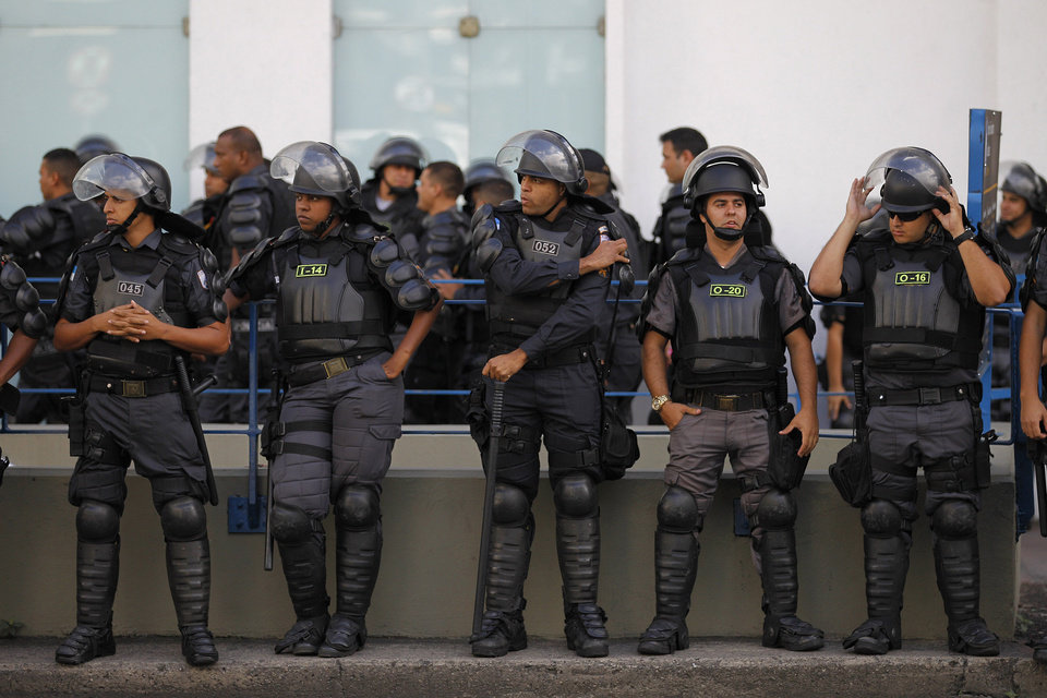 Photo - Police stand guard on the sidelines of an anti-World Cup protest near Maracana stadium on the last day of the World Cup soccer tournament in Rio de Janeiro, Brazil, Sunday, July 13, 2014. For the final match between Argentina and Germany, authorities ordered the deployment of the largest security detail in Brazil's history. (AP Photo/Leo Correa)
