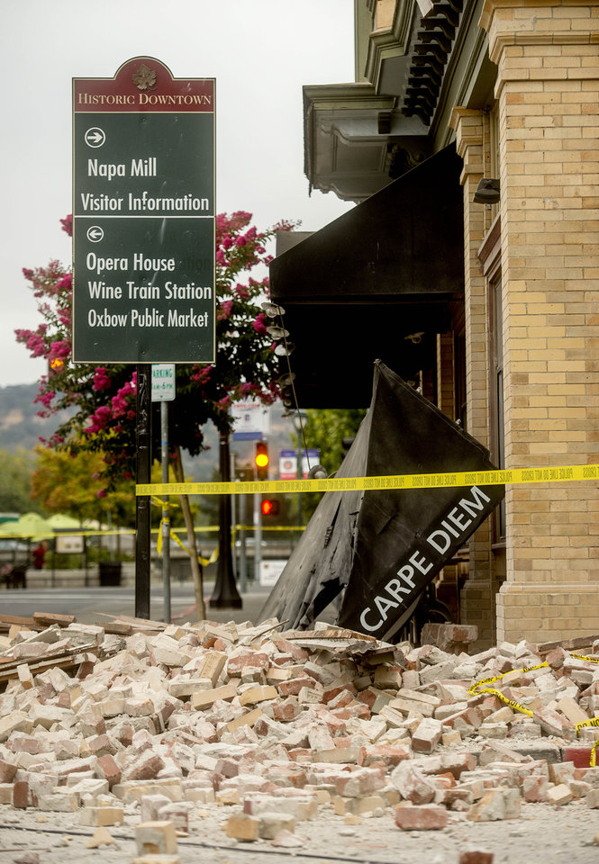 Photo - An awning for Carpe Diem wine bar sits among rubble in Napa, Calif., following an earthquake Sunday, Aug. 24, 2014. A large earthquake caused significant damage and left at least three critically injured in California's northern Bay Area early Sunday, igniting fires, sending at least 87 people to a hospital, knocking out power to tens of thousands and sending residents running out of their homes in the darkness. (AP Photo/Noah Berger)