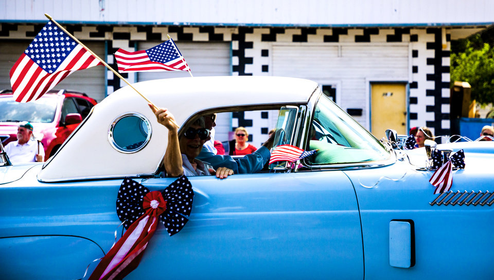 Photo - Parade participants wave American Flags  to the spectators as they drive a vintage car during the Bethany Freedom Festival parade in Bethany, Okla. on Thursday, July 4, 2019.    [Chris Landsberger/The Oklahoman]