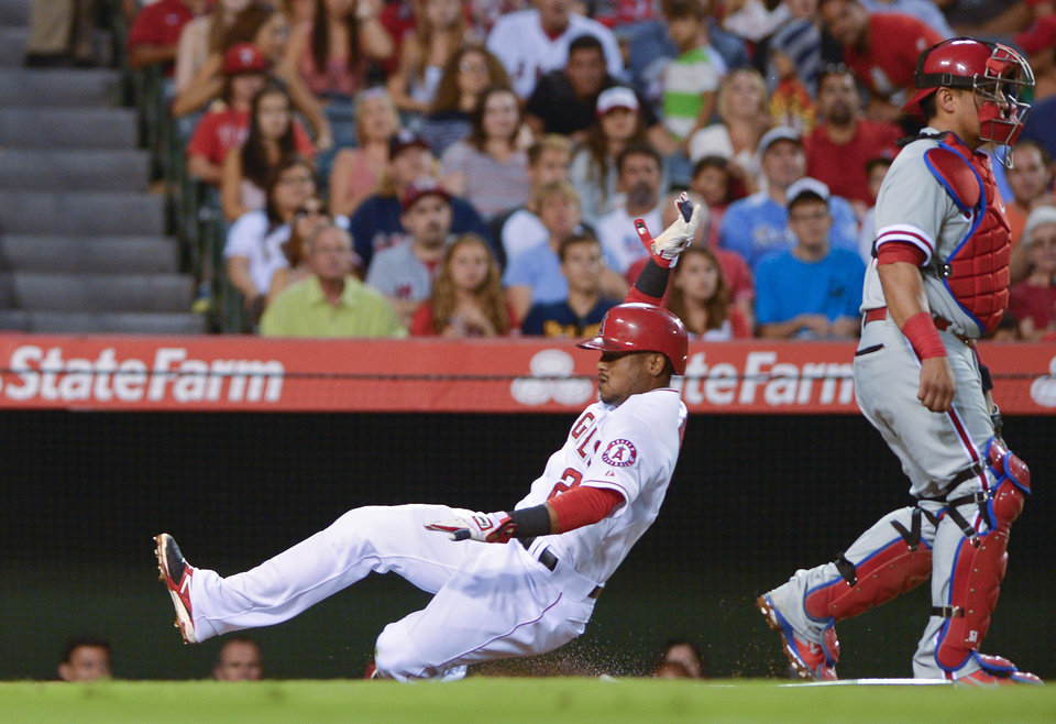 Photo - Los Angeles Angels' Erick Aybar, left, scores on a sacrifice fly by Brennan Boesch as Philadelphia Phillies catcher Carlos Ruiz looks on during the second inning of a baseball game, Wednesday, Aug. 13, 2014, in Anaheim, Calif. (AP Photo/Mark J. Terrill)