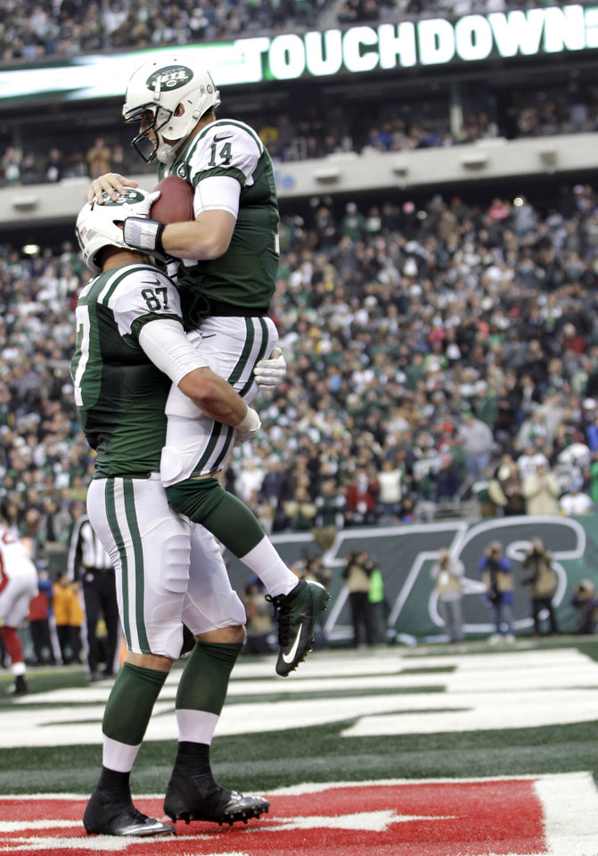 Photo - New York Jets quarterback Greg McElroy (14) is lifted by teammate Konrad Reuland after throwing a 1-yard touchdown pass to tight end Jeff Cumberland during the second half of an NFL football game against the Arizona Cardinals, Sunday, Dec. 2, 2012, in East Rutherford, N.J. (AP Photo/Kathy Willens)