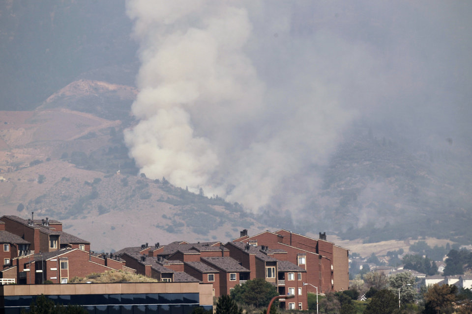 Photo -   A plume of smoke rises behind homes on the Waldo Canyon wildfire west of Colorado Springs, Colo., on Wednesday, June 27, 2012. A large number of homes were destroyed by the fire Tuesday night in subdivisions west of Colorado Springs. Authorities say it remains too dangerous for them to fully assess the damage from a destructive wildfire threatening Colorado's second-largest city. (AP Photo/Ed Andrieski)