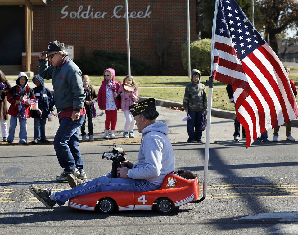 Members of VFW Post 7192 entertained people at the parade with a miniature go-cart. The city of Midwest City teamed with civic leaders and local merchants to display their appreciation for veterans and active military forces by staging a hour-long Veteran's Day parade that stretched more than a mile and a half along three of the city's busiest streets Monday morning, Nov. 12, 2012. Hundreds of people lined the parade route, many of them waving small American flags that had ben distributed by volunteers who marched near the front of the parade. A fly-over performed by F-16s from the138th Fighter Wing, Oklahoma Air National Guard unit in Tulsa thrilled spectators. Five veterans representing military personnel who served in five wars and military actions served as  Grand Marshals for the parade. Leading the parade was the Naval Reserve seven-story American flag, carried by 100 volunteers from First National Bank of Midwest City, Advantage Bank and the Tinker Federal Credit Union. The flag is 50 feet by 76 feet, weighs 110 pounds and was sponsored by the MWC Chapter of Disabled American Veterans. Photo by Jim Beckel, The Oklahoman