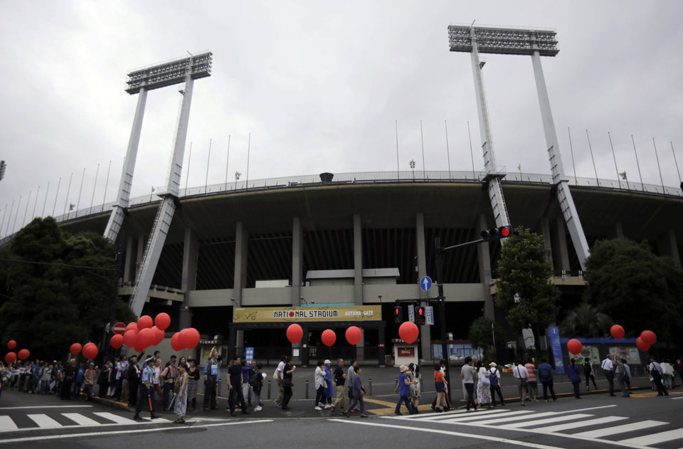 Photo - Protesters march around Tokyo's National Stadium Saturday, July 5, 2014. The group of about 500 protesters demonstrated against plans to destroy the 56-year-old facility and replace it with a colossal, futuristic structure for the 2020 Summer Olympics. (AP Photo/Eugene Hoshiko)