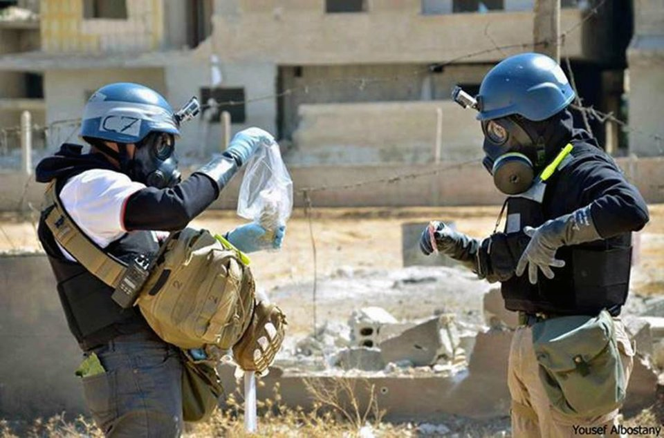 Photo - In this Aug. 28, 2013, citizen journalism image provided by the United Media Office of Arbeen which has been authenticated based on its contents and other AP reporting, members of the UN investigation team take samples from sand near a part of a missile that is likely to be one of the chemical rockets according to activists, in the Damascus countryside of Ain Terma, Syria. The U.S. government insists it has the intelligence to prove a connection between the government of President Bashar Assad to the alleged chemical weapons attack last month that killed hundreds of people in Syria_but in the absence of such evidence, Damascus and its ally Russia have aggressively pushed another scenario: that rebels carried out the Aug. 21 chemical attack. (AP Photo/United Media Office of Arbeen)