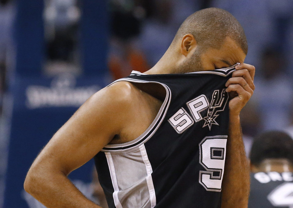 Photo - San Antonio Spurs guard Tony Parker wipes his brow between plays against the Oklahoma City Thunder in the first half of Game 6 of the Western Conference finals NBA basketball playoff series, in Oklahoma City, Saturday, May 31, 2014. (AP Photo/Sue Ogrocki)