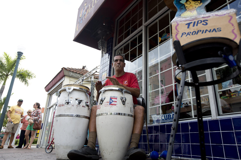 Photo - This April 30, 2014 photo shows Pablo Gonzalez Portilla playing Latin music on his drums outside a Cuban gift shop along Calle Ocho (Eighth Street) in Miami's Little Havana. Once a refuge for Cuban exiles rekindling the tastes and sounds a lost home, today Miami's Little Havana is a mosaic of cultures and a popular tourist destination. (AP Photo/J Pat Carter)
