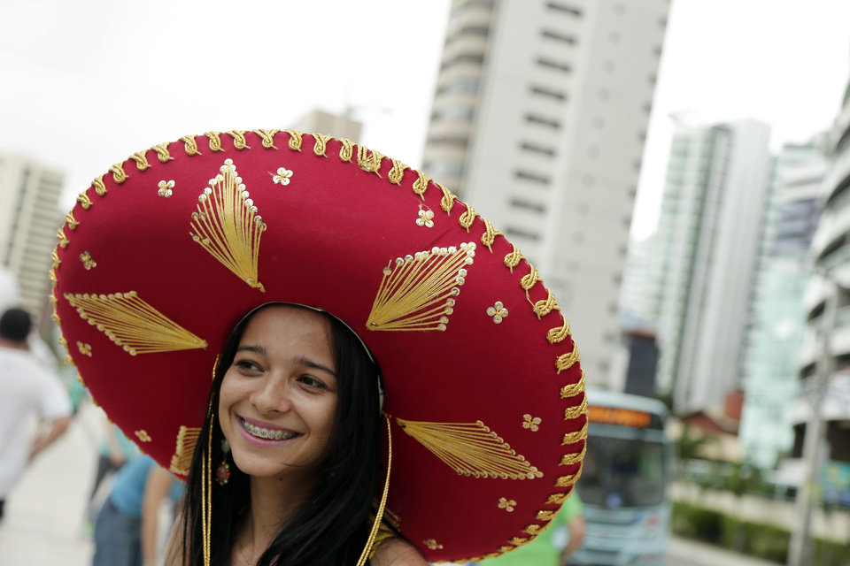 Photo - A Brazilian girl tries on a Charro hat, worn by Mexican cowboys, as she talks to a Mexico fan during the 2014 soccer World Cup in Fotaleza, Brazil, Tuesday, June 17, 2014.  Mexico faces Brazil today in Fortaleza. (AP Photo/Marcio Jose Sanchez)