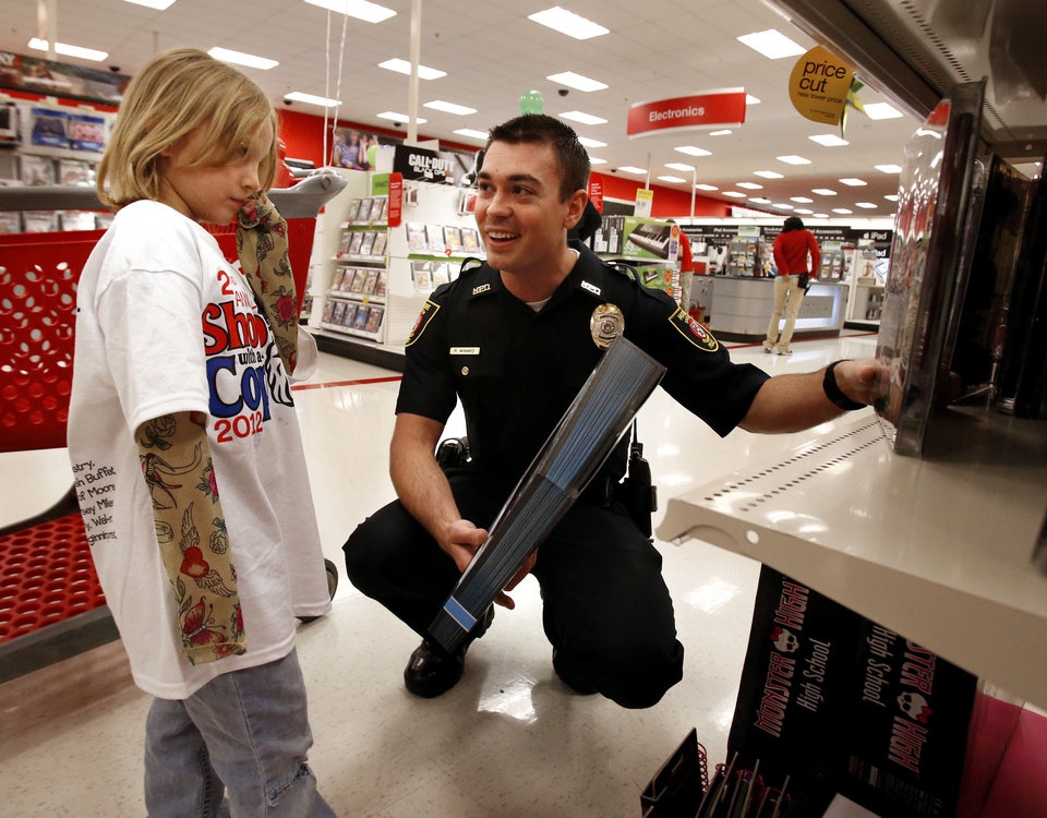"Baylee Rose Woodruff, 5, gets shopping assistance Saturday from Moore police officer Ryan Minard during ""Shop With a Cop"" in Moore."