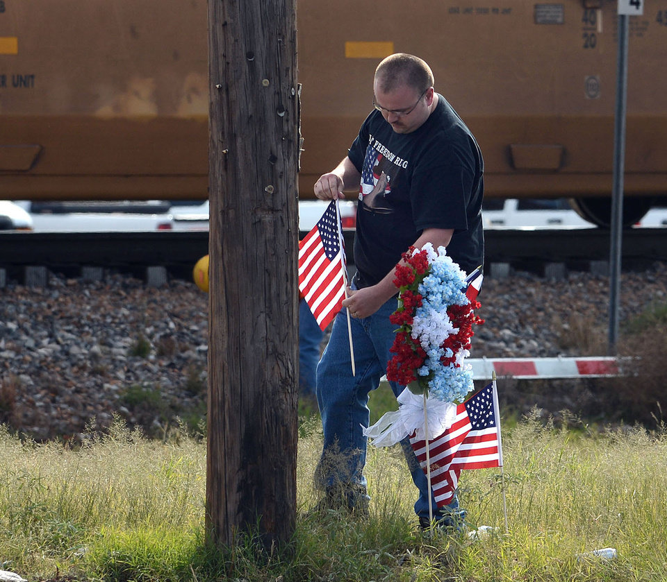 Midland, Texas resident Jerry Cook places a wreath his mother made and two U.S. flags Friday, Nov. 16, 2012 at the location where a train struck a flatbed trailer carrying veterans in a parade Thursday afternoon, killing four. (AP Photo/Odessa American, Mark Sterkel)