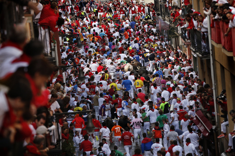 Photo - Revelers are chased by Dolores Aguirre's ranch fighting bulls during the running of the bulls of the San Fermin festival, in Pamplona, Spain, Tuesday, July 8, 2014. Revelers from around the world arrive in Pamplona take part in the eight-day running of the bulls glorified by Ernest Hemingway's 1926 novel