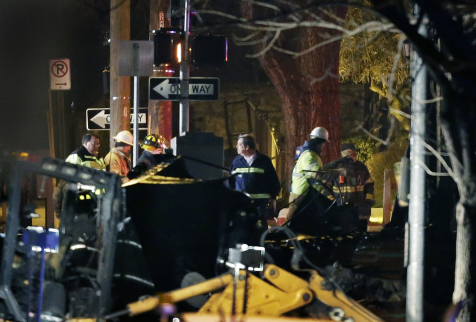 Photo - Firemen and utility workers inspect a building that exploded and caught fire in the Plaza shopping district of Kansas City, Mo., Tuesday, Feb. 19, 2013. (AP Photo/Orlin Wagner)