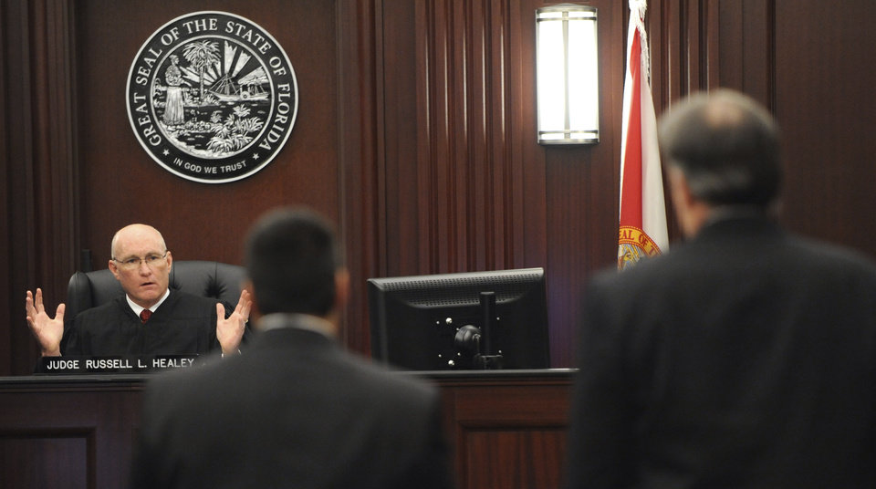 Photo - Judge Russell Healey, left rear, explains his answers to three related jury questions to defense attorney Cory Strolla, center, and defendant Michael Dunn, right, before bringing the jury into the courtroom, Saturday, Feb. 15, 2014 in Jacksonville, Fla. A jury begins their fourth day of deliberations Saturday in the trial of Dunn, who is charged with fatally shooting 17-year-old Jordan Davis after an argument over loud music outside a Jacksonville convenient store in 2012. As of Friday, they had deliberated for 22 hours over three days. (AP Photo/The Florida Times-Union, Bob Mack, Pool)