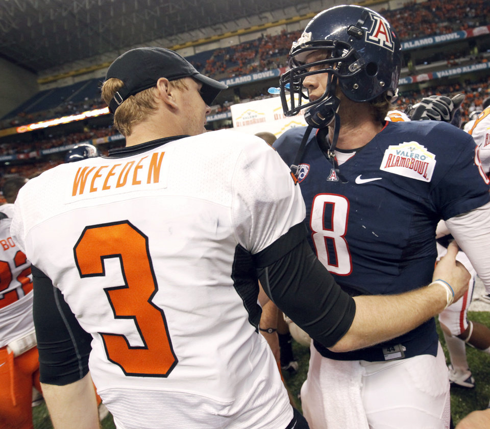 Photo - OSU quarterback Brandon Weeden (3) talks to Arizona quarterback Nick Foles (8) after the Valero Alamo Bowl college football game between the Oklahoma State University Cowboys (OSU) and the University of Arizona Wildcats at the Alamodome in San Antonio, Texas, Wednesday, December 29, 2010. OSU won, 36-10. Photo by Nate Billings, The Oklahoman