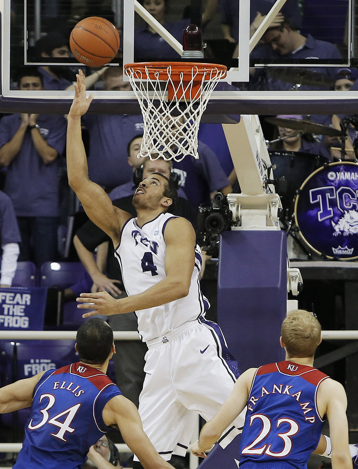Photo - TCU forward Amric Fields (4) attempts a layup as Kansas' Perry Ellis (34) and Conner Frankamp (23) defend in the first half of an NCAA college basketball game, Saturday, Jan. 25, 2014, in Fort Worth, Texas. (AP Photo/Brandon Wade)