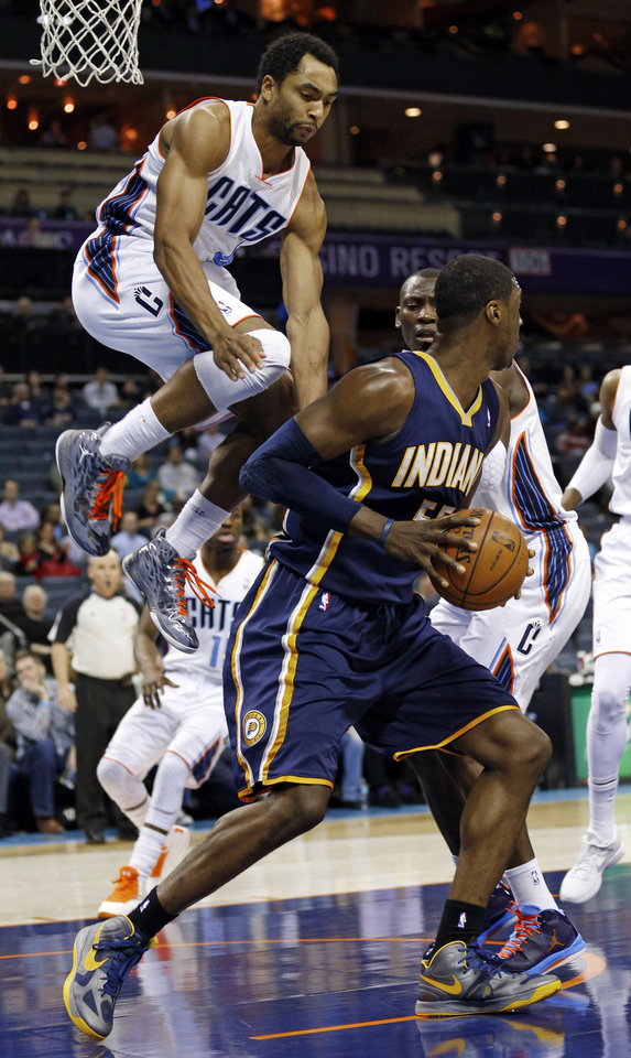 Photo - Indiana Pacers' Roy Hibbert, right, looks to pass as Charlotte Bobcats' Gerald Henderson, left, leaps high to block during the first half of an NBA basketball game in Charlotte, N.C., Tuesday, Jan. 15, 2013. (AP Photo/Chuck Burton)