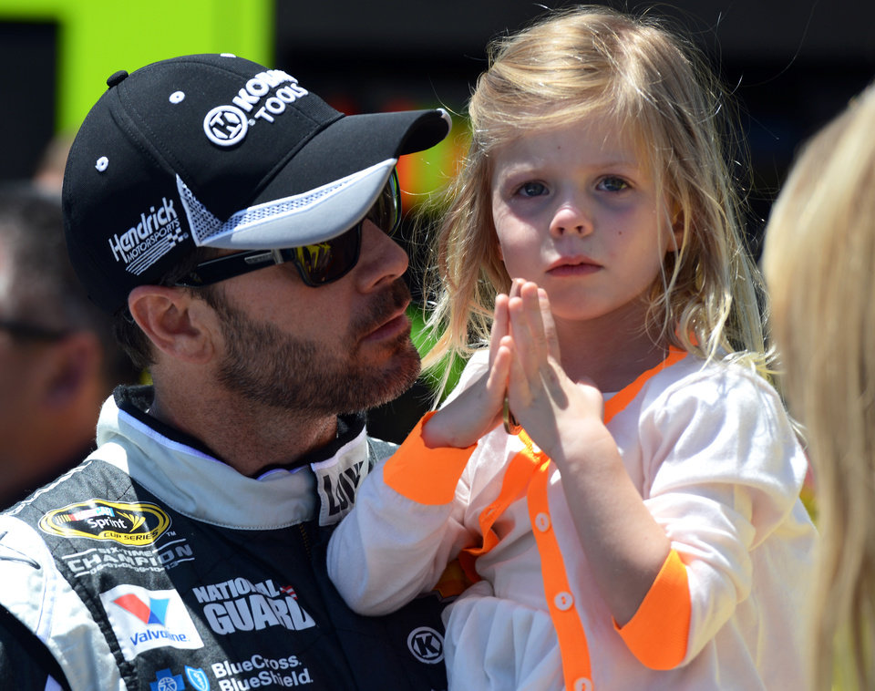 Photo - Driver Jimmie Johnson holds his daughter Genevieve, right, before driving in the NASCAR Sprint Cup series auto race at Dover International Speedway, Sunday, June 1, 2014, in Dover, Del. (AP Photo/Molly Riley)
