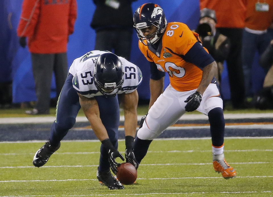 Photo - Seattle Seahawks' Malcolm Smith (53) recovers a fumble by Denver Broncos' Demaryius Thomas as Broncos' Julius Thomas (80) watches during the second half of the NFL Super Bowl XLVIII football game Sunday, Feb. 2, 2014, in East Rutherford, N.J. (AP Photo/Matt York)