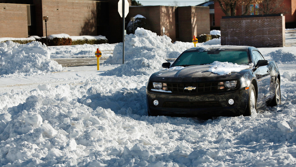 Photo - The low clearance of this  sports car caused it to become stuck in deep snow on a residential street near Reno and Air Depot in Midwest City Thursday, Feb. 3, 2011.   Photo by Jim Beckel, The Oklahoman