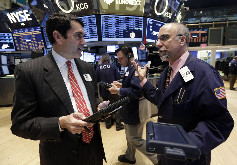 Photo - Traders Mark Muller, left, and John Liotti, right, work on the floor of the New York Stock Exchange, Monday, April 7, 2014.  Stocks are starting out the week the same way they ended the last one,  down. (AP Photo/Richard Drew)