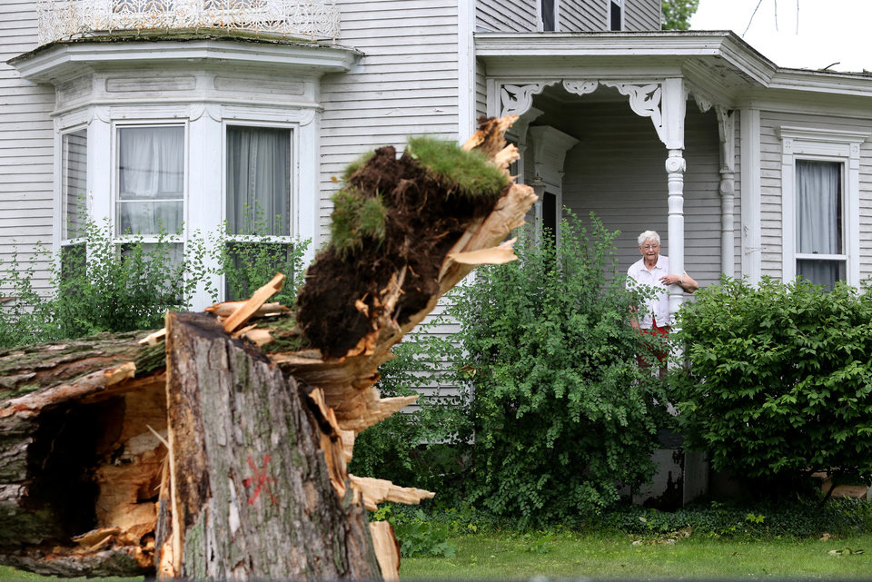 Photo - Marylane Ross looks out from the porch after a storm in Vicksburg, Mich., Tuesday, July 1, 2014. Severe thunderstorms packing high winds knocked down trees and power lines across parts of Michigan, leaving more than 230,000 without power and injuring a firefighter. (AP Photo/Kalamazoo Gazette-MLive Media Group, Mark Bugnaski) ALL LOCAL TELEVISION OUT; LOCAL TELEVISION INTERNET OUT