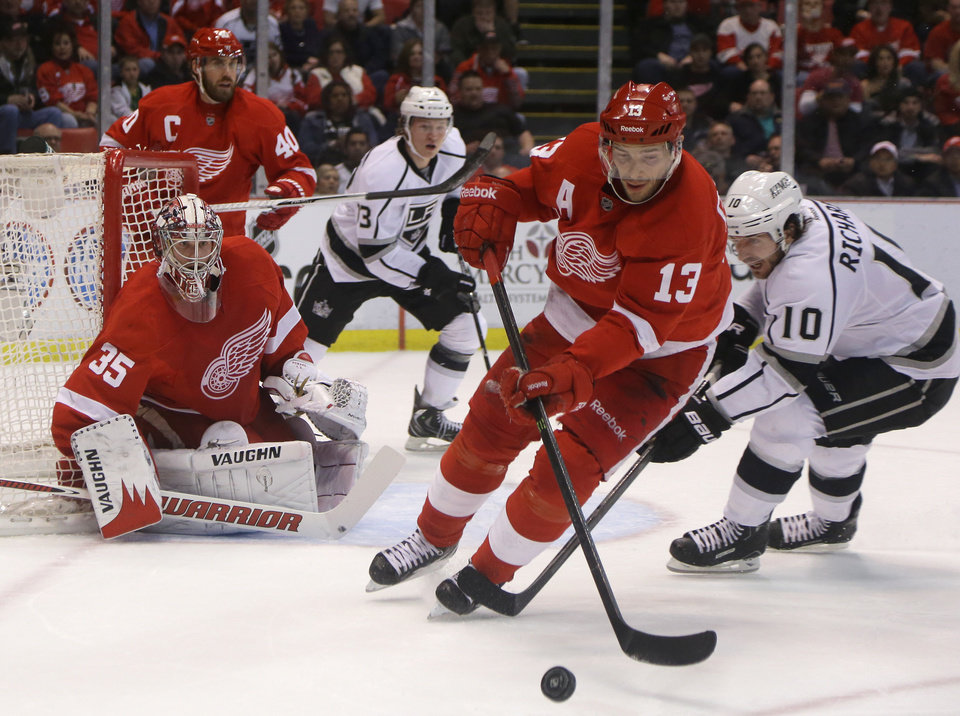 Photo - Detroit Red Wings center Pavel Datsyuk (13), of Russia, controls the puck in front of Los Angeles Kings center Mike Richards (10) during the first period of an NHL hockey game in Detroit, Wednesday, April 24, 2013. (AP Photo/Carlos Osorio)